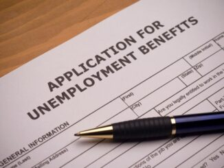 """A picture of a white piece of paper that reads in black font, """"Application for Unemployment Benefits"""" on a wooden surface."""